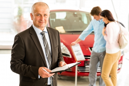 car dealer: Portrait of middle aged salesman in car retail store