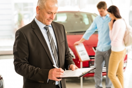 Portrait of Caucasian salesman in car showroom photo