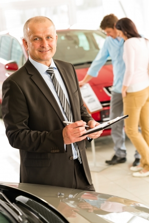 Closeup portrait of salesman working in car dealership photo