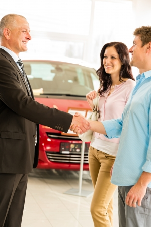 Young couple buying car from salesman shaking hands photo