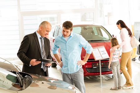 Car agent showing vehicle to young family Standard-Bild