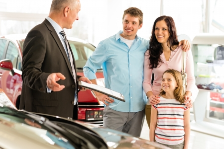 Concesionario de coches que ofrece un coche de familia sonriente Foto de archivo