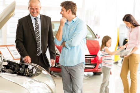 Car salesman showing the engine of the car Banque d'images