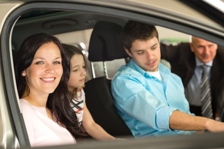 Caucasian family sitting in car in retail store photo