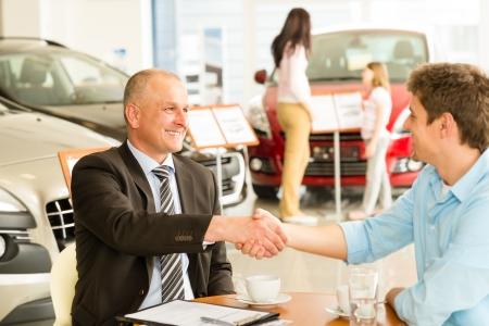 Kaukasische klant en autoverkoper handen schudden