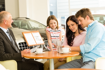 Young couple reading contract in car dealership photo