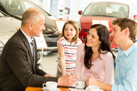 Car salesman and caucasian couple doing paperwork photo