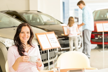 auto dealership: Female customer drinking coffee in car retail store