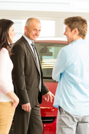 Portrait of car dealer talking with customers photo