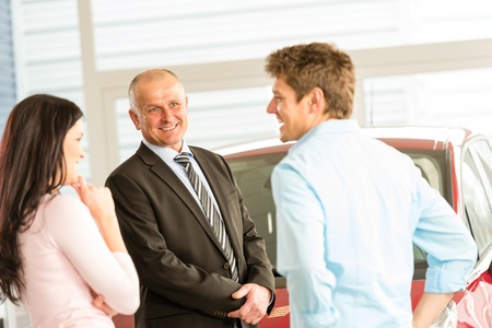Customers talking with car agent in showroom photo