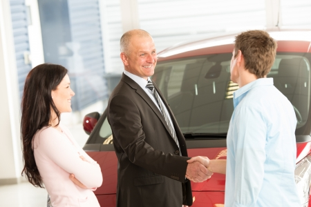 Caucasian couple purchasing a car in showroom photo