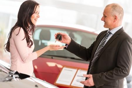 Salesman handing car keys to smiling woman Standard-Bild