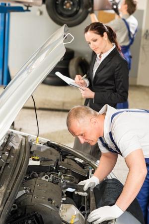 Middle aged Caucasian mechanic examining engine photo