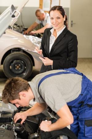 garage automobile: Mécanique et gestionnaire féminin travaillant dans un atelier de réparation Banque d'images