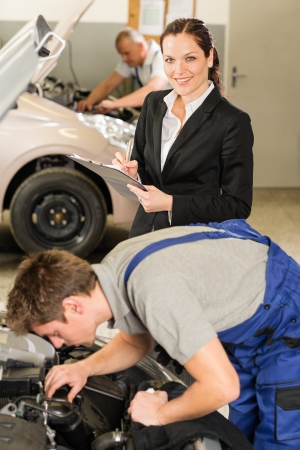 Mechanics and female manager working in repair shop photo