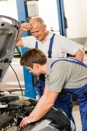 Elderly mechanic supervising young colleagues work photo
