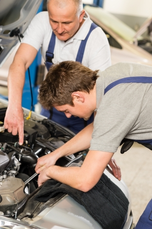 Middle aged car repairman helping colleague in garage photo
