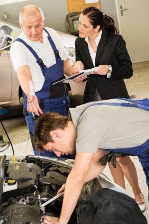 Upset female supervisor showing papers to car mechanic photo