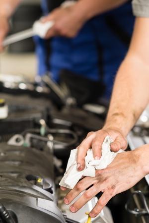 Mecánico de coche limpiándose las manos sucias con un paño Foto de archivo