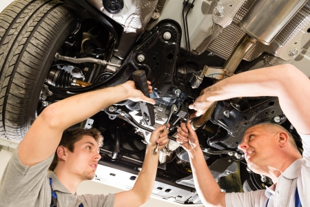 mecanico: Retrato de reparadores debajo de un coche a trabajar juntos