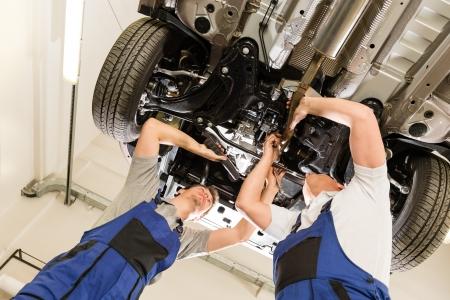 auto shop: Auto mechanics working underneath a lifted car