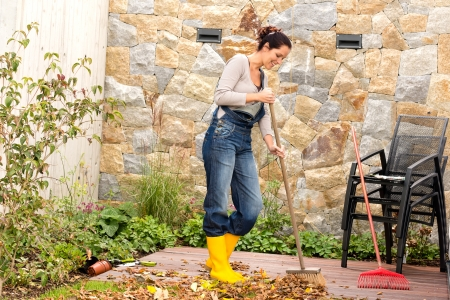 Jonge vrouw vegen herfstbladeren veranda achtertuin schoonmaken stapel