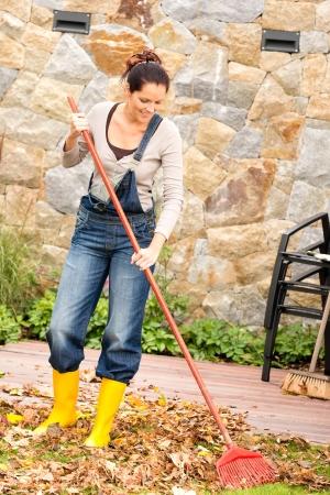 Smiling woman raking leaves autumn fall garden housework Standard-Bild