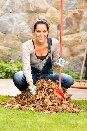 dry leaf: Cheerful woman sweeping leaves fall pile backyard housework outdoor