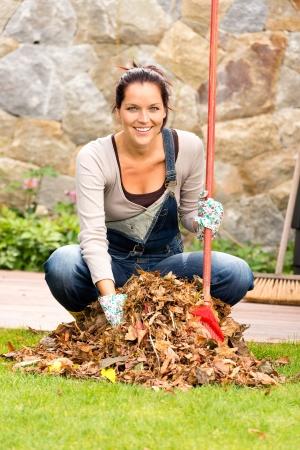Mujer alegre que barrer las hojas caen pila patio tareas domésticas al aire libre