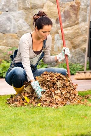 Jonge vrouw harken droge bladeren stapelen achtertuin huishoudelijk werk vallen Stockfoto