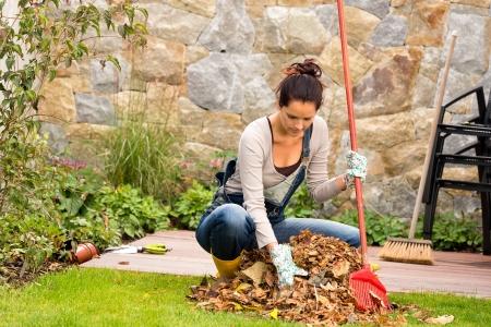 Jonge vrouw harken bladeren herfst stapel tuin veranda huishouden vegen