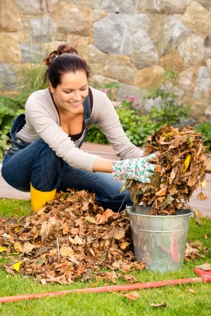 Happy woman autumn putting dry leaves bucket backyard cleaning garden