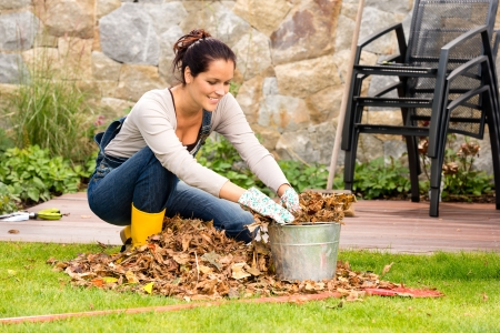 yard work: Smiling woman stuffing dry leaves into bucket autumn garden housework