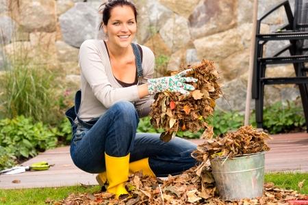 Mujer sonriente que pone en las hojas de otoño cubo jardín doméstico Foto de archivo