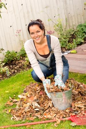 rake: Happy woman filling bucket fall leaves gardening housework rake