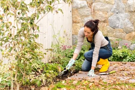 Jonge vrouw het najaar van tuinieren achtertuin plantgoed instrumenten huishouden bloembed