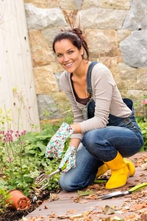 Happy woman gardening fall yard housework flowerbed hobby Stock Photo