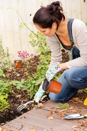 Mujer arrodillada siembra de otoño patio jardín manía rake plantas domésticas Foto de archivo