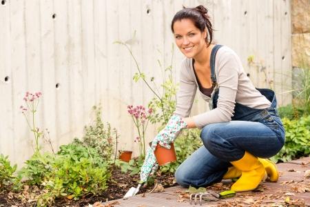 mujer arrodillada: Mujer sonriente oto�o de jardiner�a patio dom�stico man�a Foto de archivo