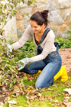 Feliz mujer jardinería clippers patio otoño pasatiempo poda de rodillas