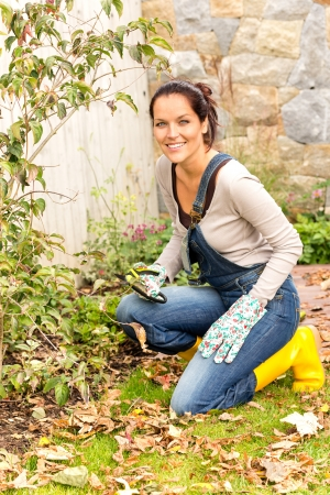 Smiling woman gardening yard fall hobby housework kneeling dry leaves photo