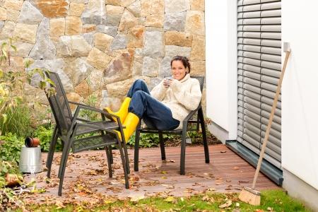 Gelukkige vrouw ontspannende najaar huishoudelijk werk koffie drinken val patio Stockfoto