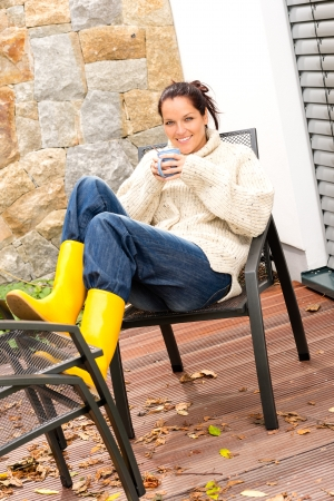Cheerful woman drinking tea cup veranda autumn relaxing photo