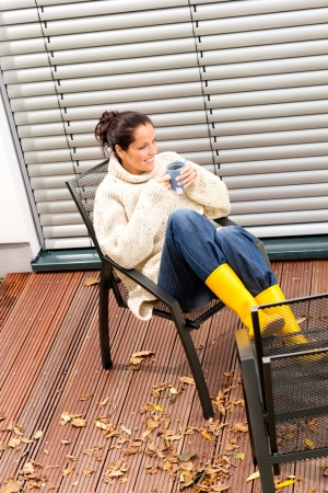 Young woman sitting drinking cup tea patio fall relaxing photo