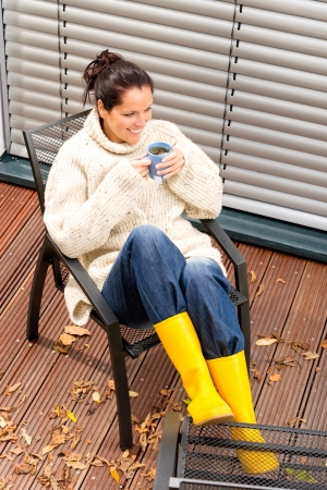Cheerful woman drinking tea backyard autumn relaxing rubber boots photo