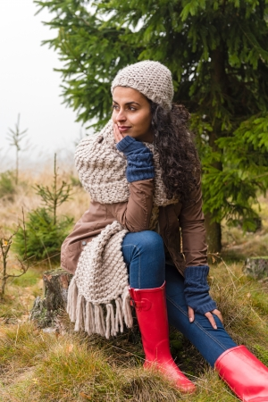 women in boots: Woman sitting on ground autumn foggy pinewood in knitted scarf Stock Photo