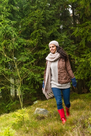 women in boots: Woman walking in pinewood autumn wear knitted scarf and hat
