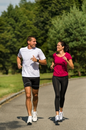 Sporty Caucasian couple running in park Stock Photo - 22212888