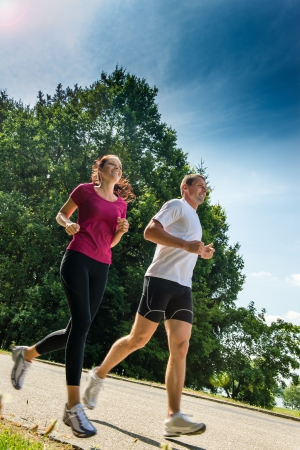 Healthy young couple jogging in a park Stock Photo - 22212913