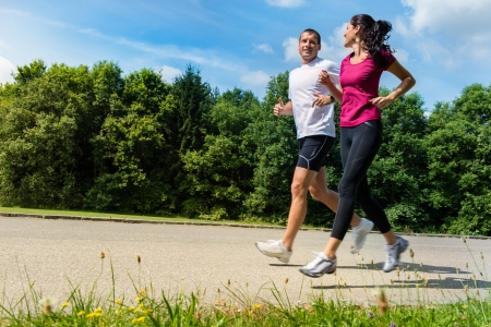 horizontal: Portrait of fit Caucasian couple running outdoors Stock Photo